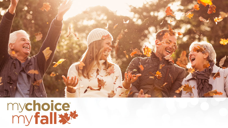younger and older couple throwing leaves in the fall with the mychoice myfall logo